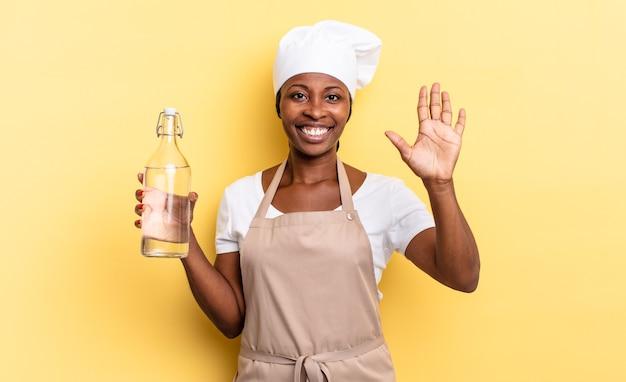 Zwarte afro-chef-vrouw die lacht en er vriendelijk uitziet, nummer vijf of vijfde toont met de hand naar voren, aftellend met een waterfles