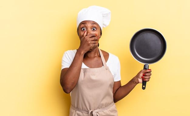 Zwarte afro-chef-vrouw die mond bedekt met handen met een geschokte, verbaasde uitdrukking, een geheim houdt of oeps zegt