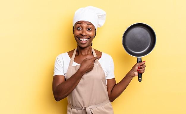 Zwarte afro-chef-vrouw die opgewonden en verrast kijkt en naar de zijkant en naar boven wijst om ruimte te kopiëren