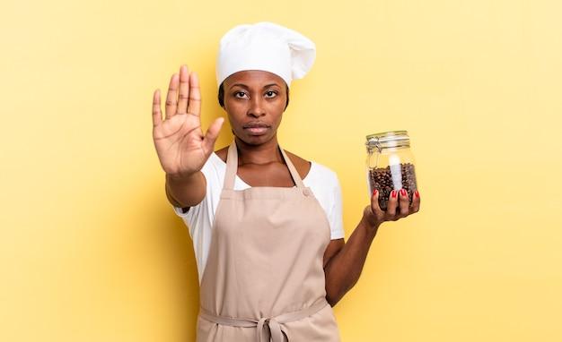 Zwarte afro-chef-vrouw die serieus, streng, ontevreden en boos kijkt en een open palm laat zien die een stopgebaar maakt. koffiebonen concept
