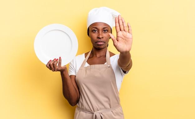 Zwarte afro-chef-vrouw die serieus, streng, ontevreden en boos kijkt en een open palm laat zien die een stopgebaar maakt. leeg bord concept