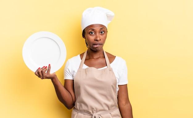 Zwarte afro-chef-vrouw die verbaasd en verward kijkt, lip bijt met een nerveus gebaar, niet wetend het antwoord op het probleem. leeg bord concept