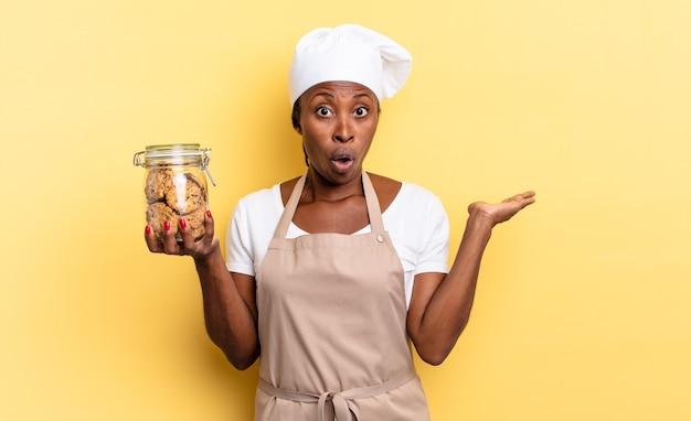 Zwarte afro-chef-vrouw die verrast en geschokt kijkt, met open mond terwijl ze een object vasthoudt met een open hand aan de zijkant. koekjes concept Premium Foto