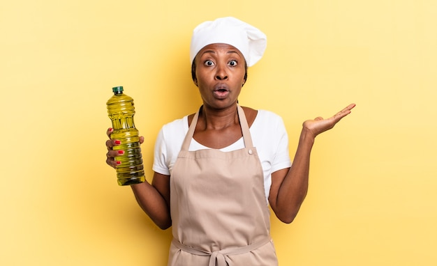 Zwarte afro-chef-vrouw die verrast en geschokt kijkt, met open mond terwijl ze een object vasthoudt met een open hand aan de zijkant. olijfolie concept