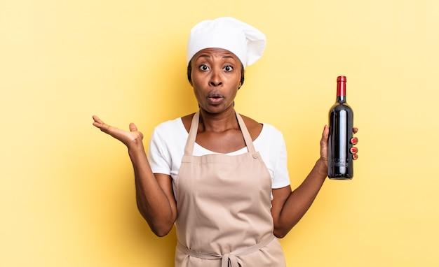 Zwarte afro-chef-vrouw die verrast en geschokt kijkt, met open mond terwijl ze een object vasthoudt met een open hand aan de zijkant. wijnfles concept
