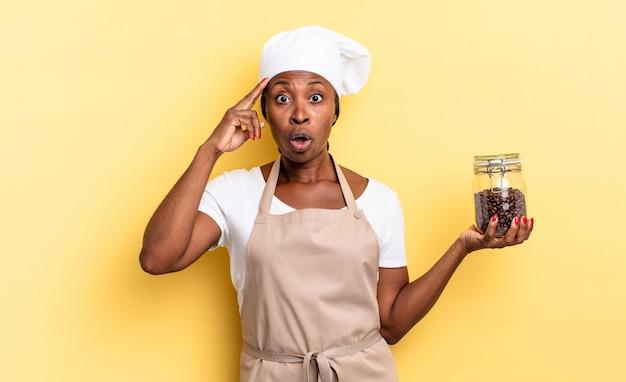 Zwarte afro-chef-vrouw die verrast, met open mond, geschokt kijkt en een nieuwe gedachte, idee of concept realiseert. koffiebonen concept