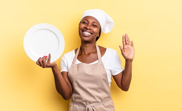 Zwarte afro-chef-vrouw die vrolijk en vrolijk lacht, met de hand zwaait, je verwelkomt en begroet, of afscheid neemt. leeg bord concept