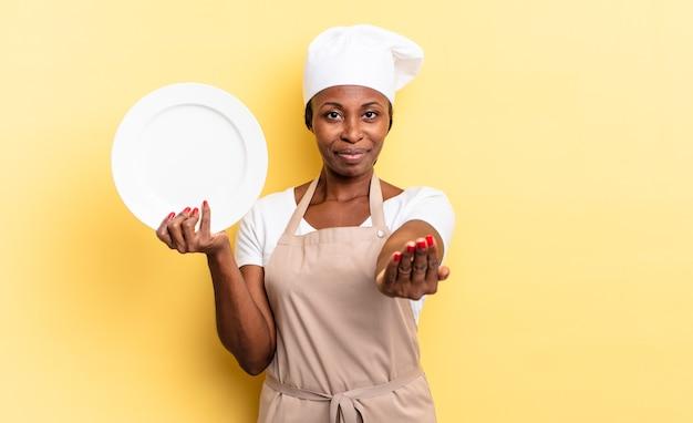 Zwarte afro-chef-vrouw die vrolijk lacht met een vriendelijke, zelfverzekerde, positieve blik, een object of concept aanbiedt en toont. leeg bord concept