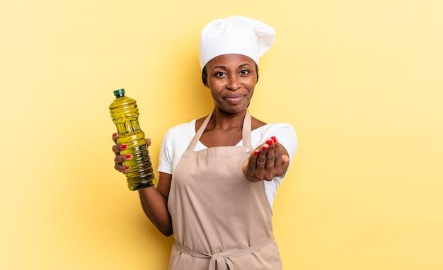 Zwarte afro-chef-vrouw die vrolijk lacht met een vriendelijke, zelfverzekerde, positieve blik, een object of concept aanbiedt en toont. olijfolie concept
