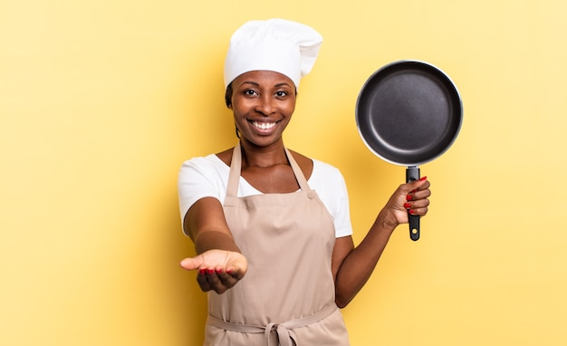 Zwarte afro-chef-vrouw die vrolijk lacht met een vriendelijke, zelfverzekerde, positieve blik, een object of concept aanbiedt en toont