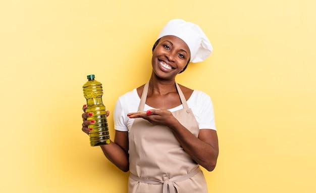 Zwarte afro-chef-vrouw die vrolijk lacht, zich gelukkig voelt en een concept in kopieerruimte toont met de palm van de hand. olijfolie concept