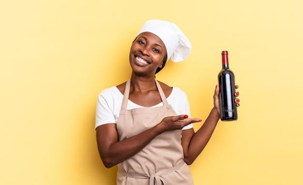 Zwarte afro-chef-vrouw die vrolijk lacht, zich gelukkig voelt en een concept in kopieerruimte toont met de palm van de hand. wijnfles concept