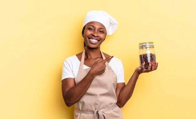 Zwarte afro-chef-vrouw die vrolijk lacht, zich gelukkig voelt en naar de zijkant en naar boven wijst, een object in de kopieerruimte laat zien. koffiebonen concept