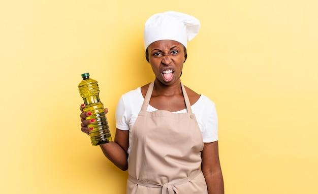 Zwarte afro-chef-vrouw die walgt en geïrriteerd voelt, tong uitsteekt, een hekel heeft aan iets smerigs en vies. olijfolie concept