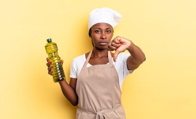 Zwarte afro-chef-vrouw die zich boos, boos, geïrriteerd, teleurgesteld of ontevreden voelt, duimen naar beneden met een serieuze blik. olijfolie concept