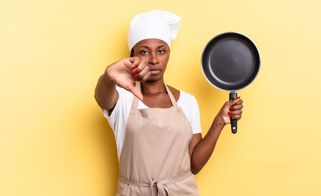 Zwarte afro-chef-vrouw die zich boos, boos, geïrriteerd, teleurgesteld of ontevreden voelt, duimen naar beneden met een serieuze blik