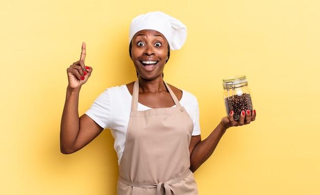 Zwarte afro-chef-vrouw die zich een gelukkig en opgewonden genie voelt na het realiseren van een idee, vrolijk vinger opstekend, eureka!. koffiebonen concept