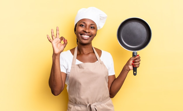 Zwarte afro-chef-vrouw die zich gelukkig, ontspannen en tevreden voelt, goedkeuring toont met een goed gebaar, glimlachend