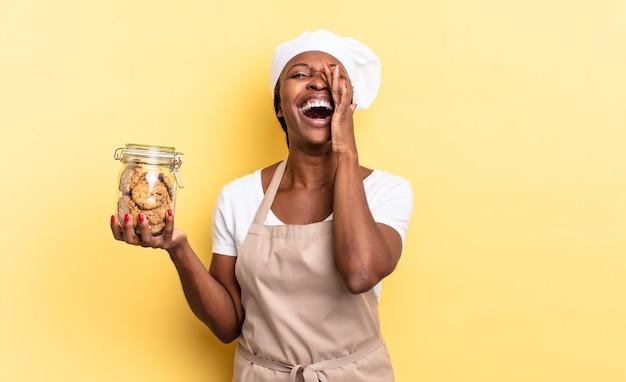 Zwarte afro-chef-vrouw die zich gelukkig, opgewonden en positief voelt, een grote schreeuw geeft met de handen naast de mond, roept. koekjes concept