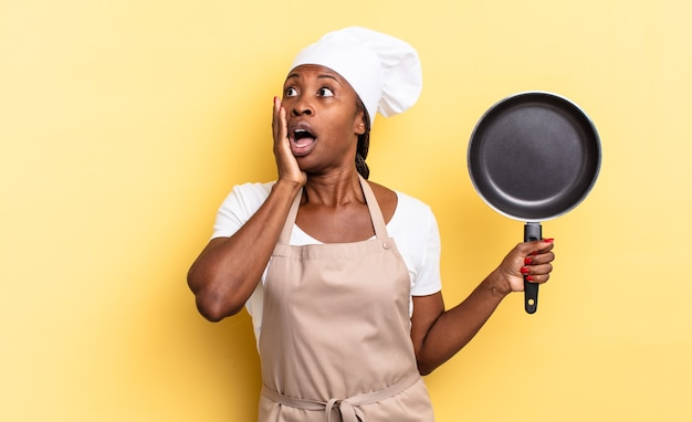 Zwarte afro-chef-vrouw die zich gelukkig, opgewonden en verrast voelt, opzij kijkend met beide handen op het gezicht