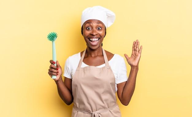 Zwarte afro-chef-vrouw die zich gelukkig, opgewonden, verrast of geschokt voelt, glimlacht en verbaasd over iets ongelooflijks. afwas concept
