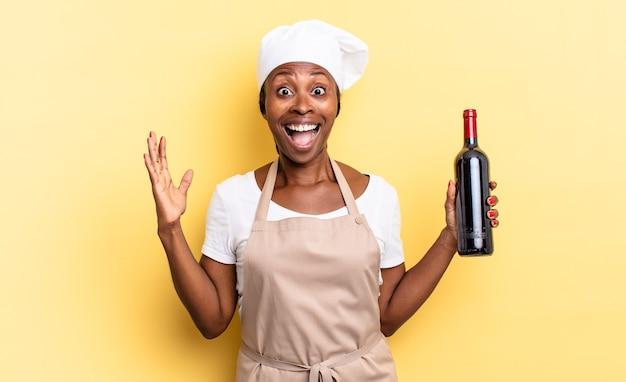 Zwarte afro-chef-vrouw die zich gelukkig, opgewonden, verrast of geschokt voelt, glimlacht en verbaasd over iets ongelooflijks. wijnfles concept