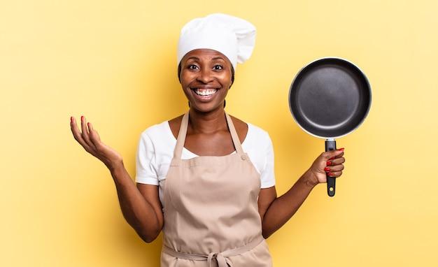 Zwarte afro-chef-vrouw die zich gelukkig, verrast en opgewekt voelt, lacht met een positieve houding, een oplossing of idee realiseert