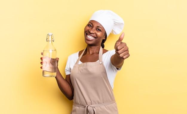 Zwarte afro-chef-vrouw die zich trots, zorgeloos, zelfverzekerd en gelukkig voelt, positief lacht met duimen omhoog met een waterfles
