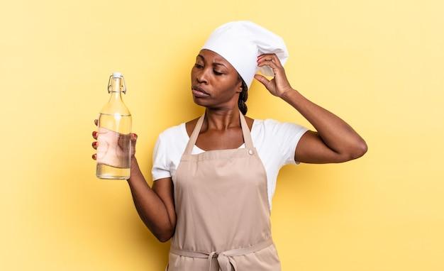 Zwarte afro-chef-vrouw die zich verbaasd en verward voelt, haar hoofd krabt en naar de zijkant kijkt met een waterfles