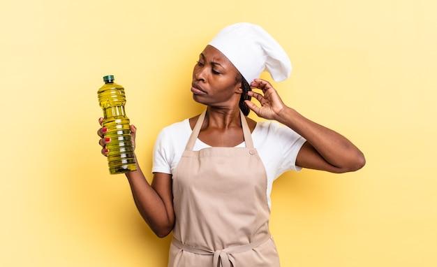 Zwarte afro-chef-vrouw die zich verbaasd en verward voelt, hoofd krabt en opzij kijkt. olijfolie concept