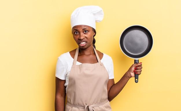 Zwarte afro-chef-vrouw die zich verbaasd en verward voelt, met een stomme, verbijsterde uitdrukking die naar iets onverwachts kijkt