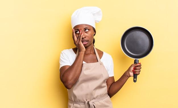 Zwarte afro-chef-vrouw die zich verveeld, gefrustreerd en slaperig voelt na een vermoeiende, saaie en vervelende taak, gezicht met de hand vasthoudend