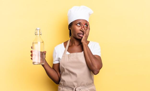 Zwarte afro-chef-vrouw die zich verveeld, gefrustreerd en slaperig voelt na een vermoeiende, saaie en vervelende taak, gezicht vasthoudend met de hand met een waterfles