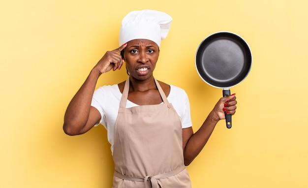 Zwarte afro-chef-vrouw die zich verward en verbaasd voelt en laat zien dat je gek, gek of gek bent