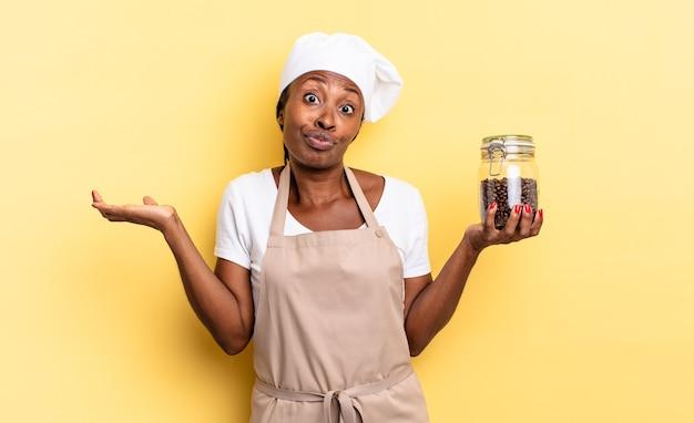 Zwarte afro-chef-vrouw die zich verward en verward voelt, twijfelt, weegt of verschillende opties kiest met grappige uitdrukking. koffiebonen concept