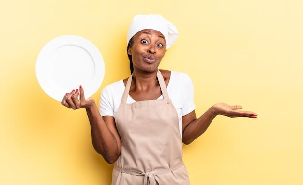 Zwarte afro-chef-vrouw die zich verward en verward voelt, twijfelt, weegt of verschillende opties kiest met grappige uitdrukking. leeg bord concept