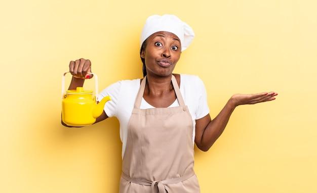 Zwarte afro-chef-vrouw die zich verward en verward voelt, twijfelt, weegt of verschillende opties kiest met grappige uitdrukking. theepot concept