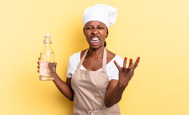 Zwarte afro-chef-vrouw kijkt boos, geïrriteerd en gefrustreerd schreeuwend wtf of wat is er mis met jou die een waterfles vasthoudt