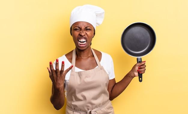 Zwarte afro-chef-vrouw kijkt boos, geïrriteerd en gefrustreerd schreeuwend wtf of wat is er mis met jou