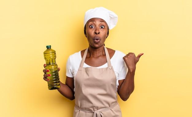 Zwarte afro-chef-vrouw kijkt verbaasd in ongeloof, wijst naar een object aan de zijkant en zegt wauw, ongelooflijk. olijfolie concept