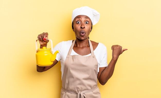 Zwarte afro-chef-vrouw kijkt verbaasd in ongeloof, wijst naar een object aan de zijkant en zegt wauw, ongelooflijk. theepot concept