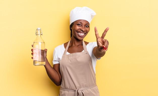 Zwarte afro-chef-vrouw lacht en ziet er gelukkig, zorgeloos en positief uit, gebaart overwinning of vrede met één hand die een waterfles vasthoudt