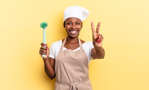 Zwarte afro-chef-vrouw lacht en ziet er vriendelijk uit, nummer twee of seconde met de hand naar voren, aftellend. afwas concept