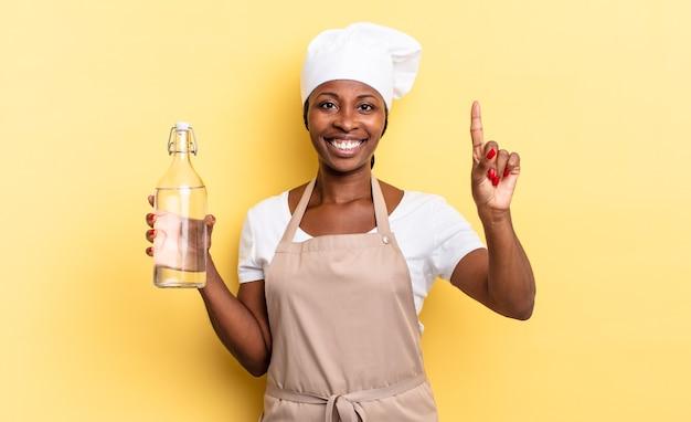 Zwarte afro-chef-vrouw lacht en ziet er vriendelijk uit, toont nummer één of eerste met hand naar voren, aftellend met een waterfles