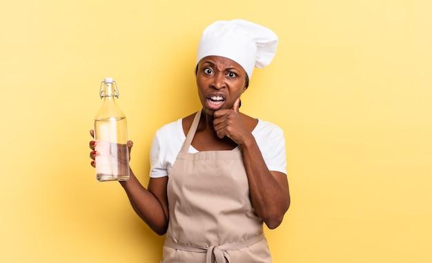 Zwarte afro-chef-vrouw met mond en ogen wijd open en hand op kin, onaangenaam geschokt voelen, wat zeggen of wauw met een waterfles