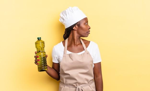 Zwarte afro-chef-vrouw op profielweergave die ruimte vooruit wil kopiëren, denken, fantaseren of dagdromen. olijfolie concept