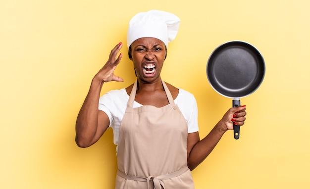 Zwarte afro-chef-vrouw schreeuwt met handen in de lucht, voelt zich woedend, gefrustreerd, gestrest en overstuur