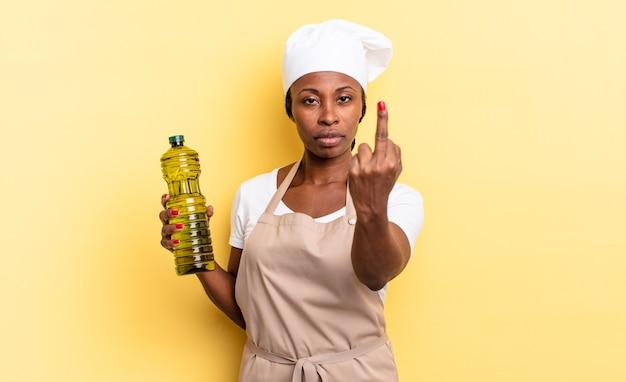 Zwarte afro-chef-vrouw voelt zich boos, geïrriteerd, opstandig en agressief, draait de middelvinger om en vecht terug. olijfolie concept