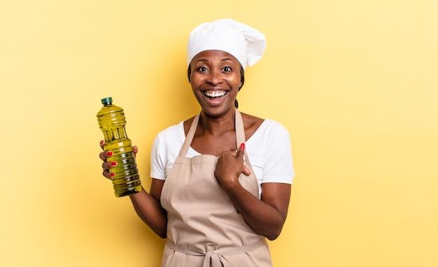 Zwarte afro-chef-vrouw voelt zich gelukkig, verrast en trots, wijzend naar zichzelf met een opgewonden, verbaasde blik. olijfolie concept