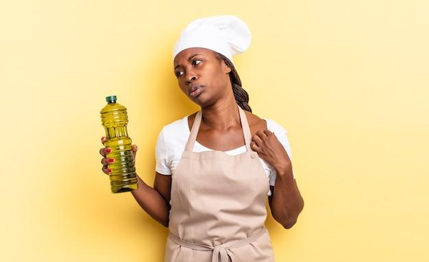 Zwarte afro-chef-vrouw voelt zich gestrest, angstig, moe en gefrustreerd, trekt aan de nek van het shirt, ziet er gefrustreerd uit met een probleem. olijfolie concept